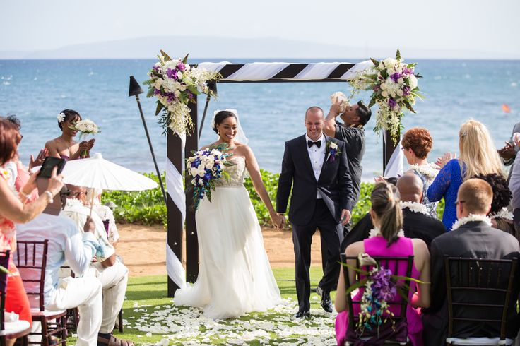 Beautiful large floral bouquets adorn this Maui wedding canopy.