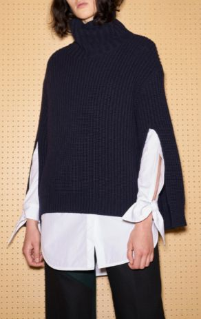 Shop now. Eudon Choi Carvalho Jumper. Long sleeved ribbed knit jumper, with open back in a navy colour. Has a relaxed fit, featuring a turtleneck and slit detail on sleeves.