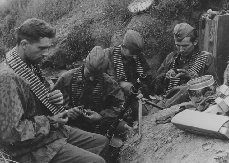 Four SS soldiers with ammunition belts in a trench near Leningrad, 1942. An MG 34 machine gun can be seen in the middle of them.