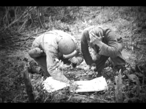 Cameraman: Lee / Weiner / Tampone. Unités: 5th ESB / 1st Army. Date: 7, 8 et 9 juin 1944.  Omaha Beach / Colleville-sur-Mer / Blosville / Carquebut.  Thèmes: Prisonnier / LST / Plage / Planeur Horsa / Cimetière provisoire / Repas / Char / Tombe / Cadavre / Enfant fleur / Femme fleur / Vieuw couple vin ou Calvados ou Cidre