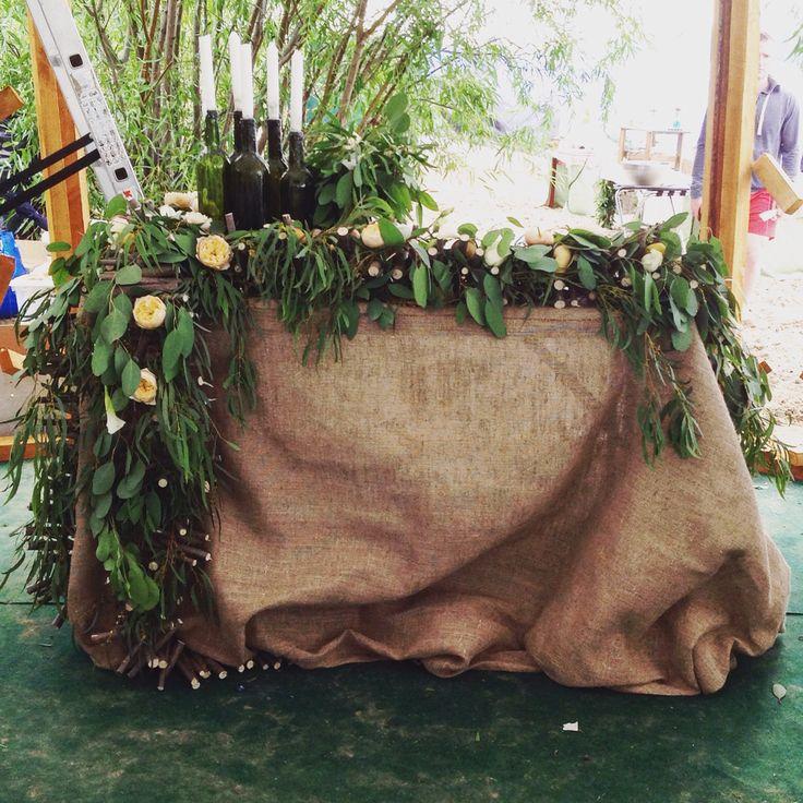 Стол жениха и невесты украшен гирляндой из орешника ,роз Вувузелла ,эвкалипта и нектаринами
