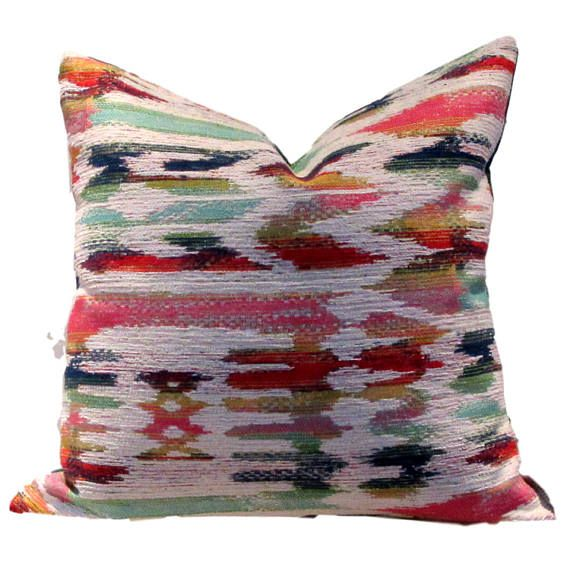Vibrant clear colours in this multi coloured ikat on white background. Bright pink, turquoise, teal, navy, green, yellow and orange, red and white. Has a very bohemian feel. Reverse is sewn in co-ordinating heavy teal linen 100% polyester SEWN BY US IN CANADA PILLOW COVER ONLY with zippered closure All interior seams are reinforced and sewn corners are tapered to avoid dog ears dry cleaning recommended With large patterns, pattern placement will vary. Please let us know when you order sh...