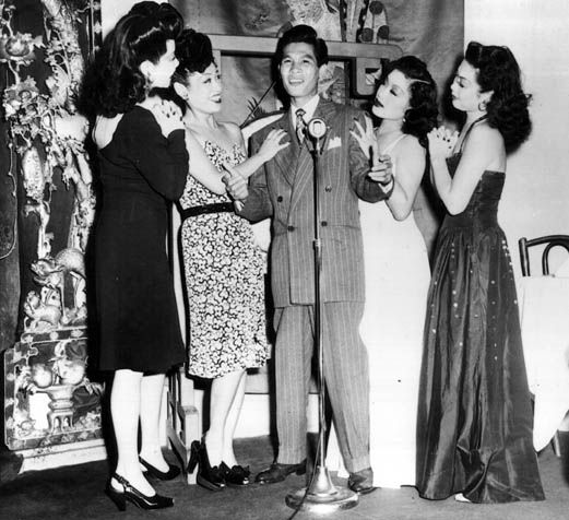 """Larry Ching, often referred to as the """"Chinese Frank Sinatra,"""" sings to adoring chorus girls. """"Forbidden City: The Golden Age of Chinese Nightclubs."""""""