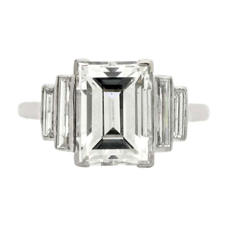 Art Deco diamond ring, circa 1935. Set to centre with a rectangle step cut diamond, 2.62 carats, I colour, VS2 clarity, in an open back corner claw setting, flanked by four vertically set rectangle baguette cut diamonds in open back rubover settings with an approximate combined weight of 0.50 carats. Platinum