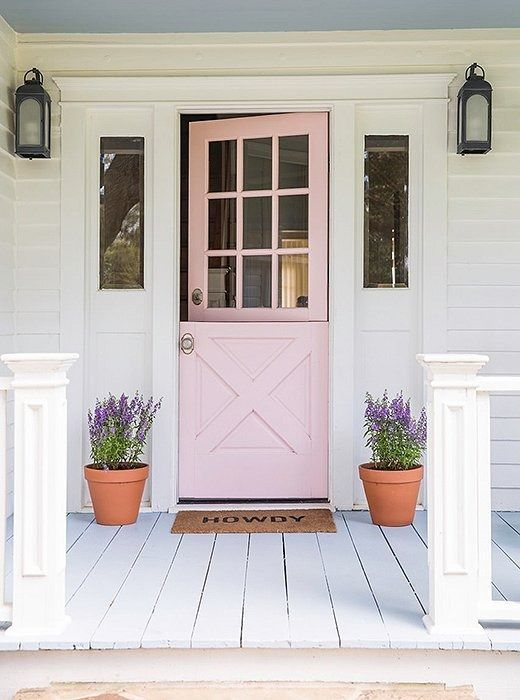 Giving your home curb appeal doesn't necessarily mean going all-out. Sometimes the simplest approach is the best approach. Here, a painted door flanked by lanterns and terracotta pots creates a light, lovely, and inviting look.