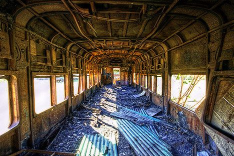 burnt out, rusted and utterly destroyed interior of an abandoned rail car in an undisclosed location