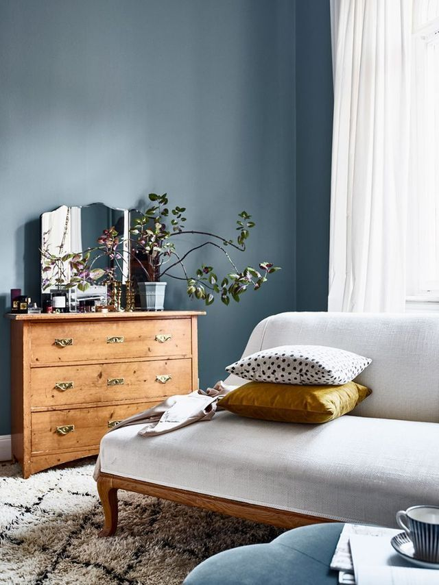 grey blue walls, french-style love seat, vintage chest of drawers, vintage mirror