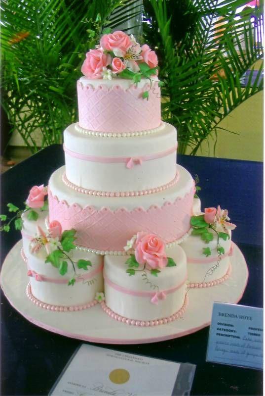 Fondant covered cake with sugar dough flower arrangements.http://www.brenscakes.com/weddingcakes.html#