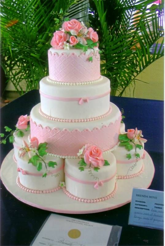 Fondant covered cake with sugar dough flower arrangements.http://www.brenscakes.com/weddingcakes.html#
