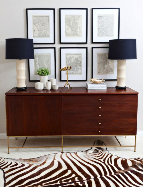 Zebra Rug - interesting combo with the bamboo shaped lamps, mid-century cabinet and nautical charts.  I like it!