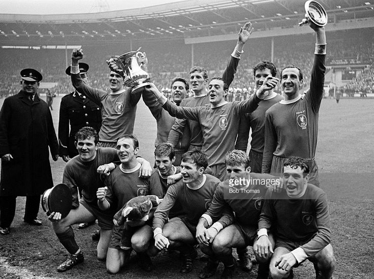 The Liverpool team, back row, left to right, Ron Yeats, Gordon Milne, Willie Stevenson, Ian St John, Chris Lawler and Gerry Byrne, front row, left to right, Tommy Lawrence, Peter Thompson, Geoff Strong, Tommy Smith, Roger Hunt and Ian Callaghan celebrate with the trophy after the Liverpool v Leeds United FA Cup Final held at Wembley Stadium, London on the 1st May 1965. Liverpool won the match 2-1 after extra time.