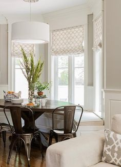 Transitional bay window breakfast nook is filled with a bay window bench under windows dressed in white and tan wedding circles roman shade facing an oval trestle dining table lined with Tolix Chairs illuminated by a white drum pendant.