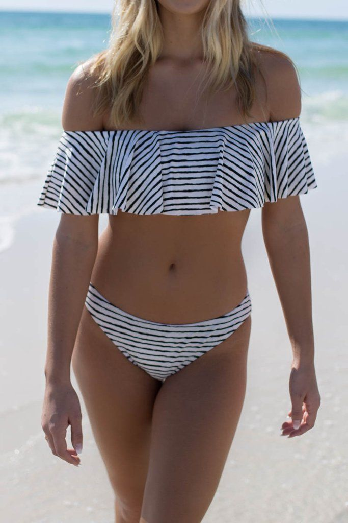 A striped bandeau bikini featuring ruffled overlay, off the shoulder details with sleeves, built in padding, and lining Striped bikini bottoms with lining Mater