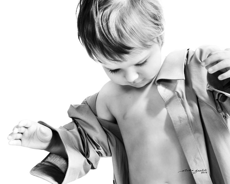 A black and white portrait of a boy in a daddy´s shirt.