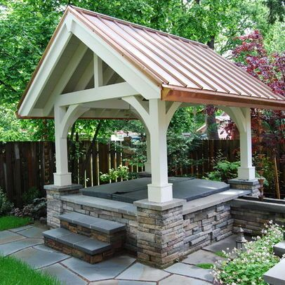 A Gazebo w/ copper roof, stone facade + great posts + beams hides an above ground hot tub. Great steps made from stacked stone w/ large blue stone tops, as well as the edge around the hot tub looks like blue stone with the runnels going out the right corner. . .
