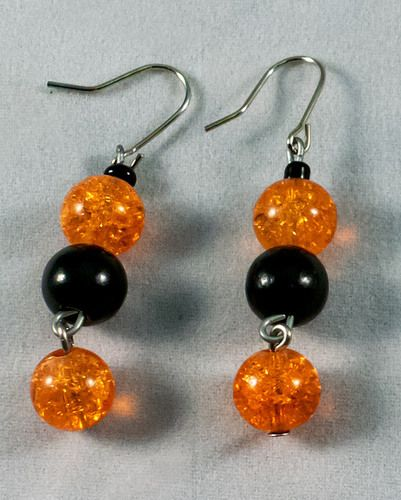 These are beautiful earrings made of black and orange beads. The earrings measure at 2.5 cm.