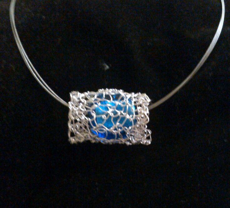 Colgante de alambre y cristal realizado en crochet. El cristal interior contiene brillos de plata craquelada.