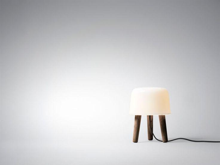 Milk, bordslampa formgiven av NORM architects för &Tradition. Milk sprider ett trivsamt sken genom sin vita skärm i munblåst opalglas och dess mjuka former och naturnära material gör hela dess uppenbarelse skön att vila ögonen på. Valet av klassiskt nordiska material som glas och trä gör att lampan enkelt finner en plats i ditt hem.