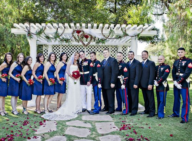 The bridesmaid's dresses pop with the uniforms in this red and blue military wedding. Great choice with that deep shade of blue and red bouquet for contrast