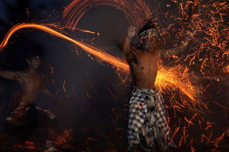 A Balinese man hits another with fire during a ritual ahead of Nyepi day in Ubud Gianyar, Bali, Indonesia. Nyepi is a day of silence to celebrate the Balinese new year, reserved for self-reflection, where people are not allowed to use lights, light fires, work, travel nor enjoy entertainment.