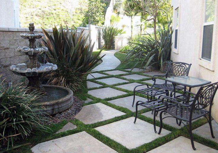 Gray concrete paver patio with grass border and backyard fountain