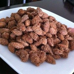 Pecans are baked in a sweet cinnamon coating, creating tasty candied pecans perfect for holiday gifts.