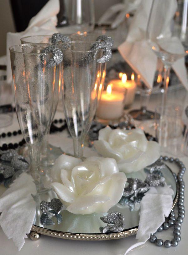 Juhlakattaus valkomustana ja rönsyilevänä. Dunin kuohuviinilasit ja ruusi-kynttilät. via http://www.haat.fi/blogit/ammattilainen-hadissaan/kattauskokeilujen-maailma-aukenee