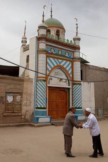 Two Uighur men greet each other in front of a small mosque in the back street neighborhoods of Hotan.