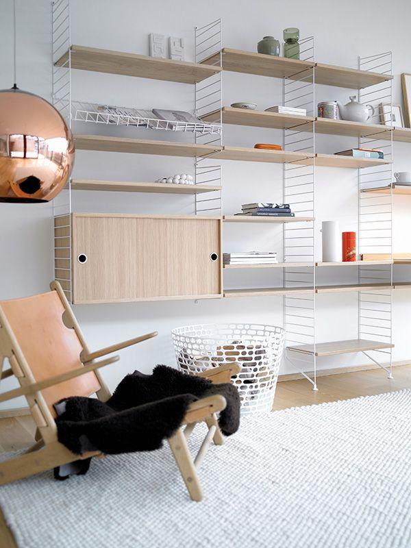 La vida nórdica a la manera String: estantes y cabinet en roble, soportes y revistero en metal blanco.