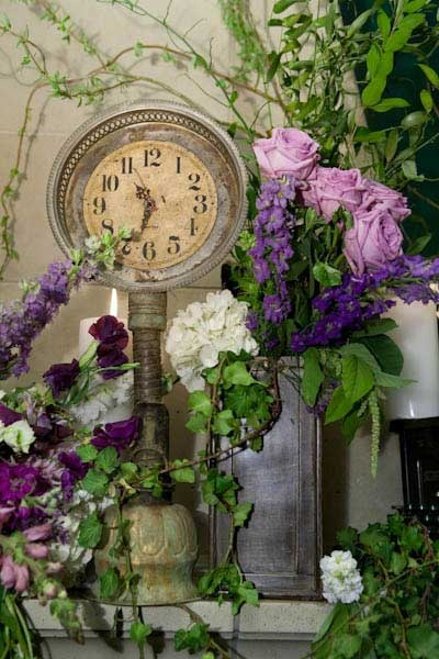 Vintage Clock surrounded by green & purple flowers on the mantel.