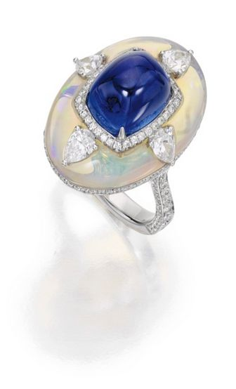 18 Karat White Gold, Opal, Sapphire and Diamond Ring:  Centering a cushion-cut cabochon sapphire weighing 8.31 carats, mounted atop an opal weighing 8.13 carats, further accented with round and pear-shaped diamonds weighing 1.65 carats, size 6.