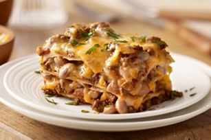Our Favorite Mexican-Style Lasagna recipe - Create a little fusion with ooey-gooey cheese, beans and taco beef layered up and baked like lasagna.