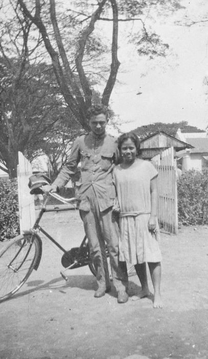 Portrait of a KNIL soldier on bicycle with his local girlfriend
