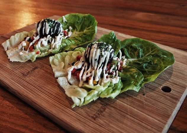 """Lettuce """"taco boats."""" Two massive leaves of crisp Romaine -- each topped with a scoop of house-made mango-tomato salsa and a delicious mushroom-feta meatball. Finished with lines of a thick and creamy sake-teriyaki sauce."""