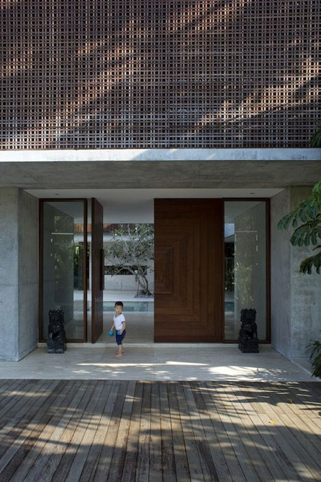 A perforated concrete wall screens the courtyard of this Singapore house.