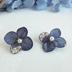 花びらの美しさと遊び心…カジュアルからフオーマルにもマッチするアクセサリーに。ミルキーベースのホワイトは通年とおしていろいろなシーンに活用いただけます。プリザーブド加工された紫陽花にレジン及びアクリル加工をし花弁1枚にスワロフスキーやベージュのパールをのせ華やかな雰囲気と落ち着き感があり品があります。ご購入の際は、備考欄にイヤリング又はピアスのご指定をお願い致します。サイズは、20㎜前後ぐらいです。