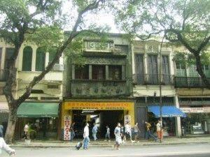 """Localizado bem no centro da cidade do Rio de Janeiro, na rua Marechal Floriano, é surpreendente ver a fachada do prédio abandonada… Nele, lê-se claramente: """"CINE FLORIANO"""", já desativado há muito tempo. No primeiro piso, funciona um """"moderno"""" estacionamento"""