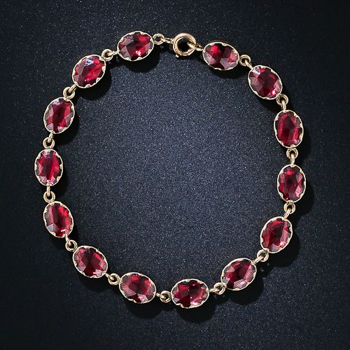 Georgian garnet bracelet. A rare and ravishing, early nineteenth century French bracelet glowing with fourteen oval rose-cut garnets set in closed-back scalloped collet settings. 7 inches long, 18 karat gold.
