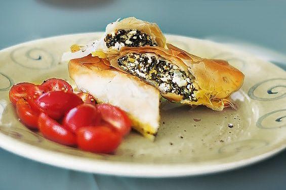 Skölj och blanchera spenaten. Pressa därefter ur all vätska och hacka den. Bryn vårlöken i olivolja. Ta kastrullen från värmen och rör ned Fetaost, spenat, vispade ägg, salt och peppar. Rulla ut filodegen på bordet, pensla med smält smör och dela varje ark i mitten. Lägg 1 msk fetaostblandning på varje remsa, vik in kanterna …
