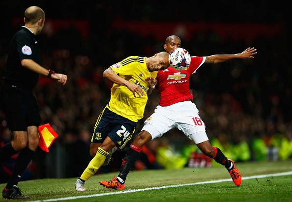 Emilio Nsue of Middlesbrough is tackled by Ashley Young of Manchester United during the Capital One Cup Fourth Round match between Manchester United...