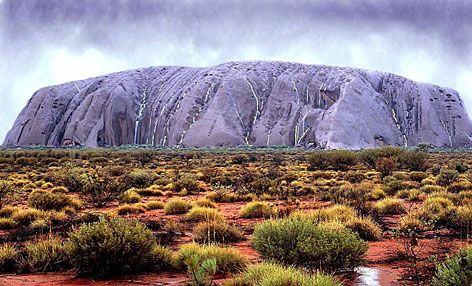Ayers Rock (Uluru) takes on an unusual color as waterfalls cascade down its walls