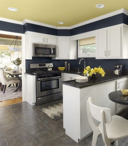 Add cheer to a white kitchen with bold colours. Keep counters clear of excess clutter for a polished look. In this urban-chic kitchen, Benjamin Moore Marblehead Gold (HC-11) pairs with Polo Blue (2062-10) to provide a new take on the traditional black-and-white colour scheme.