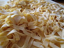 "Fettuccine (pronounced; literally ""little ribbons"" in Italian) is a type of pasta popular in Roman cuisine. It is a flat thick noodle made of egg and flour (usually one egg for every 100 g of flour), wider than but similar to the tagliatelle typical of Bologna. It is often eaten with beef ragù an chicken ragù.  Fettuccine is traditionally made fresh (either at home or commercially) but dried fettuccine can also be bought in shops.  Spinach fettuccine are made from spinach, flour, and eggs."