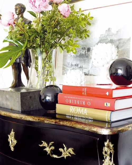 An asymmetrical arrangement on the coffee table can include a tall vase of flowers balanced with a stack of books with a decorative item placed on top. Description from livinator.com.