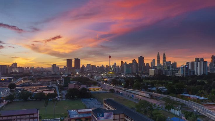 Time lapse: Beautiful and dramatic sunset view of the Kuala Lumpur skyline overlooking the busy city streets. Pan Right Motion Timelapse.