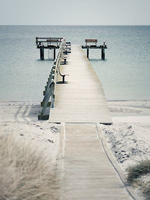 Martin Pålsson - Ljunghusen. A photo of a sandy beach with a wooden pier.