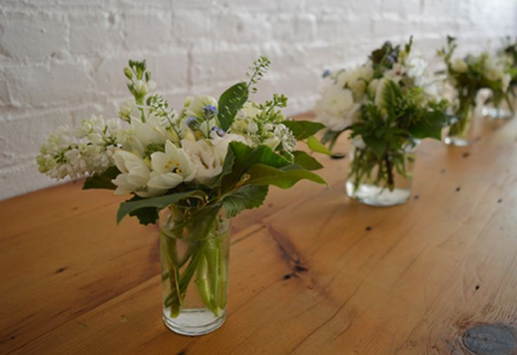 Table arrangements w/ white french lilac, parrot tulips, freesia.