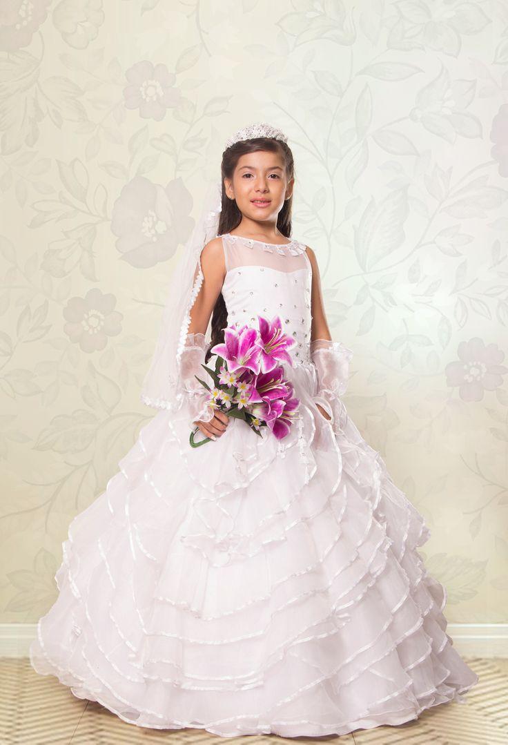 REF.14-35 Vestido de primera comunión entero, cuello redondo y manga sisa. En la parte superior del vestido una sutil transparencia con pedrería. Su falda forma hermosos boleros. Incluye guantes y velo.
