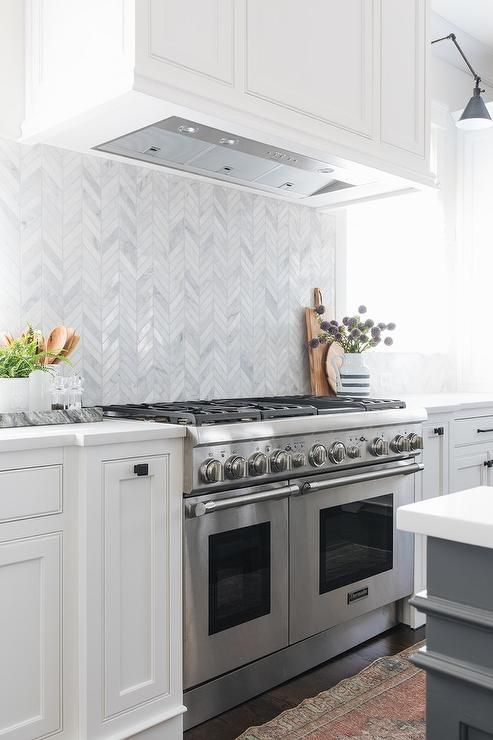 A White Wood Panel Hood Mounted To A Marble Herringbone Backsplash