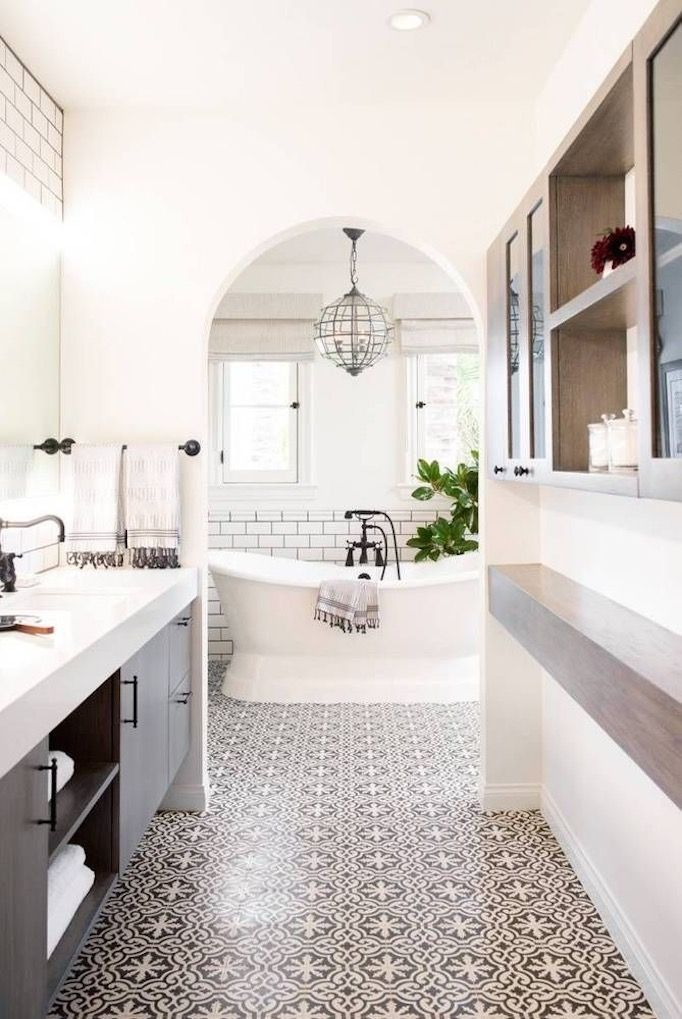 Black and white tile bathroom. This arched doorway creates a beautiful view of the white freestanding tub. I love the black and white tile flooring. It's a beautiful, artistic element in this space.